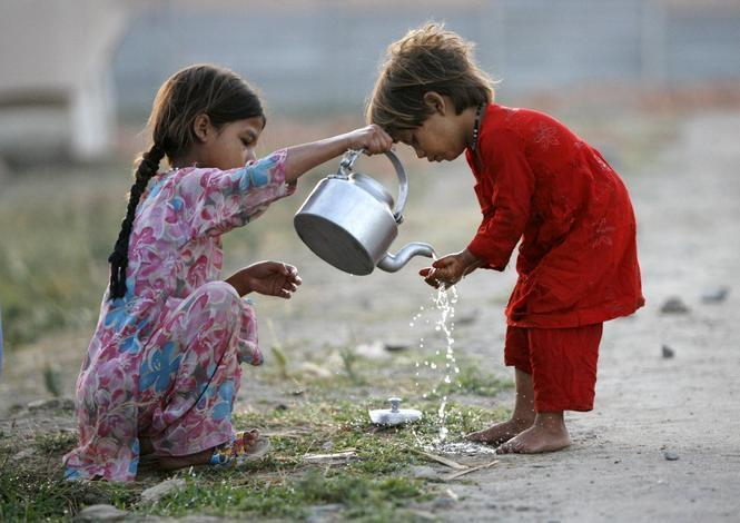 Internally displaced girls help each other wash hands at the UNHCR Sheik Shahzad camp in Mardan district